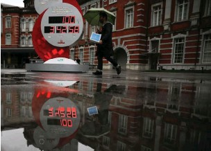 ?? ISSEI KATO/REUTERS ?? A countdown clock showing that 100 days are left until Tokyo Olympics is reflected in a puddle in Tokyo, Japan, on April 14, 2021.