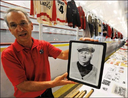 ?? CLIFFORD SKARSTEDT Examiner ?? General manager Murray Henderson with a portrait of former Lakefield police Chief Garnet Samis as part of the Lakefield Hockey 50th Anniversary Reunion Saturday at Lakefield-Smith Community Centre following a golf tournament at Katchiwano Golf Club....