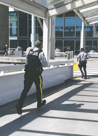 ?? SUBMITTED PHOTO ?? Police officers respond to the shooting of known gangster Karman Grewal on Sunday afternoon at Vancouver airport. The suspects fled in a Honda Pilot, later found burning in Surrey.