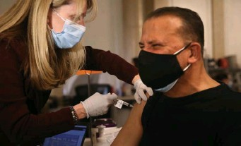 ?? NAncy lAnE / hErAld stAFF ?? 'WEIGHT LIFTED': Tufts Medical Center RN Gina Arie Giarusso gives the Johnson & Johnson COVID-19 vaccine to Hector Rosario in Boston on Thursday.