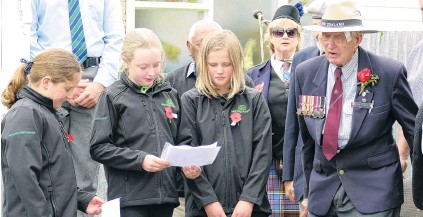 ?? PHOTO: RICHARD DAVISON ?? In remembrance . . . West Otago RSA senior member Bill Roulston (99) reads a section of For the Fallen with West Otago Rural Kids members (from left) Isla Ottrey, PeytonRose Young and Jessie Lindale (all 10), during yesterday's Armistice Day service in Tapanui.