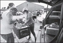 ?? ALEXA WELCH EDLUND/ TIMES-DISPATCH ?? In late August, two volunteers helped load a car at the Chesterfield Food Bank. The pandemic has increased demand for food assistance.