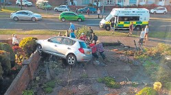 ?? Picture: Ross Sherret. ?? Neighbours help right the car which crashed into a garden in South Parks Road, Glenrothes.