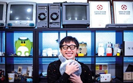 ??  ?? Aoki hugging robotic cushion Qoobo in a studio in Tokyo.