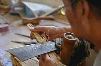 ??  ?? 制扇者用锋利的扇刀给扇骨做造型