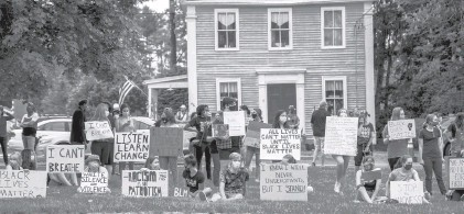 ?? KASSI JACKSON/HARTFORD COURANT ?? Protesters hold signs on the Tolland Green in a demonstration against police brutality on June 3, 2020, in Tolland.