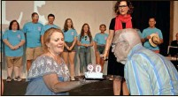 "?? Doug Walker ?? Gordon Leiter, a Rome Lit­tle Theatre sup­porter for 51 years, got the honor of blow­ing out the can­dles on the theater's 90th birthday cake Satur­day. The slice of cake is be­ing held by RLT Board Pres­i­dent Suzanne Clonts. The cast of ""Mama Mia!"" watches from the stage."