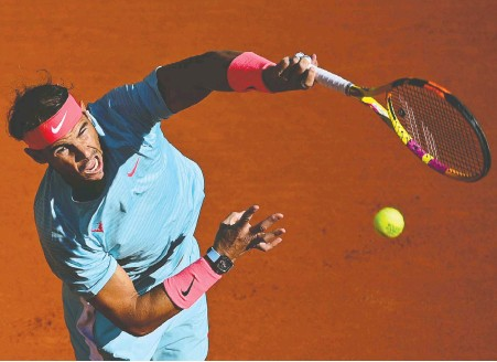 ?? MARTIN BUREAU/AFP VIA GETTY IMAGES ?? Spain's Rafael Nadal serves to American Sebastian Korda on his way to an easy 6-1, 6-1, 6-2 victory during their men's singles fourth round match on Day 8 of the 2020 French Open in Paris on Sunday.