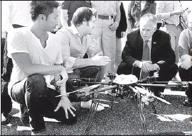 ?? David Crigger The Bristol Herald- Courier ?? TOM BASS, left, and CEOMatthew Sweeny of Flirtey show Virginia Gov. Terry McAuliffe the drone that was used to flymedicine to a health fair last week.
