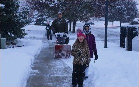 ?? MEDIANEWS GROUP FILE PHOTO ?? In this file photo, Trevor Austin works to clear snow from in front of his Macomb Township house during a November, 2019 snowfall while his daughters enjoy playing. That won't be the scene on Christmas Day, forecasters say.