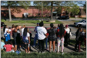 ?? (AP/Wade Payne) ?? People gather Monday outside Austin-East Magnet High School in Knoxville, Tenn.