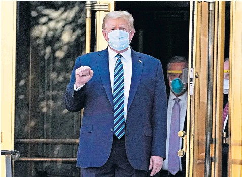 ??  ?? Walk­ing out of the hos­pi­tal shortly af­ter 6.30pm lo­cal time, Don­ald Trump, wear­ing a blue sur­gi­cal mask, pumps his fist be­fore giv­ing the thumbs-up to wait­ing pho­tog­ra­phers