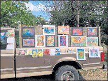 ?? Blair Chandler / Courtesy photo ?? The watercolor art of Boulder-based artist Blair Chandler is displayed on a pickup truck in front of her home at 2205 Emerald Road in September. Blair and her husband Peter Chandler, a wood carver, have been hosting weekly art pop-ups in their yard and displaying work on a large fence that surrounds the property. The next event will take place noon-4 p.m. Sunday. All work is for sale.