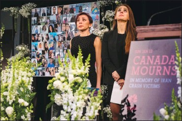 ?? Canadian Press photo ?? Banafsheh Taherian, left, and Kyan Nademi from Tirgan stand on stage during a memorial organized by the Iranian-Canadian charity Tirgan for the victims of the Iranian air crash, in Toronto, Sunday.