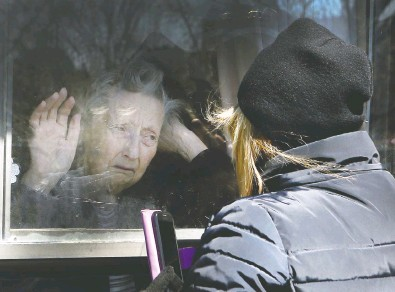 ?? VERONICA HENRI / POSTMEDIA NEWS FILES ?? Diane Colangelo visits her 86-year-old mother Patricia through a window at the Orchard Villa long-term care home in Pickering not long after the COVID pandemic began in 2020. Both daughter and mother were in tears.