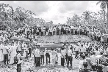 ?? Carl Court Getty Images ?? COFFINS are carried to a mass grave in Negombo, the majority Catholic town that saw 108 congregants killed during Easter Mass at St. Sebastian's Church. So many bodies had to be buried that a new cemetery was dug.