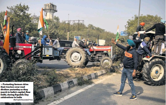?? Altaf Qadri/Associated Press ?? Protesting farmers drive their tractors over road dividers yesterday as they march to India's capital, New Delhi, during Republic Day celebrations in India