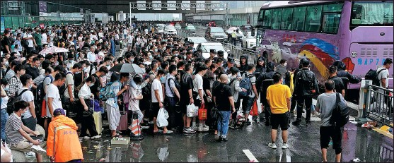?? LI AN / XINHUA ?? Stranded train passengers line up to board a bus at Zhengzhou East Railway Station in Zhengzhou, Henan province, on Wednesday. The city has been lashed by record rainfall, which has halted rail services. Buses transferred the stranded passengers to a rest center in the city.