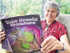 ?? PHOTO: RICHARD DAVISON ?? Hot topic . . . Jan Johnstone, of Puerua, near Balclutha, checks a copy of her newly published climate changethemed children's book, Two Greedy Monsters, at her home yesterday.