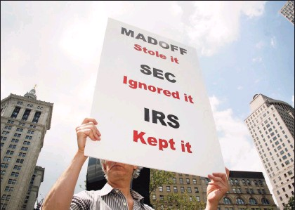 ?? Associated Press ?? A man holding a sign in protest of Bernard Madoff in June 2009, near the courthouse complex where Madoff was sentenced to 150 years for fraud scheme. Until Madoff's Ponzi scheme came crashing down the SEC esteemed him as a prominent Wall Street figure, failing to heed warnings and credible complaints over 10 years.