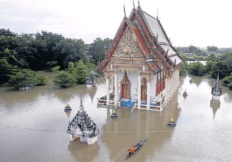 ?? THANARAK KHOONTON ?? A monk commutes by boat to receive alms as Tha Phanit temple in Kabin Buri district, Prachin Buri, is ravaged by floods. Many locations including the temple were under up to two metres of water.