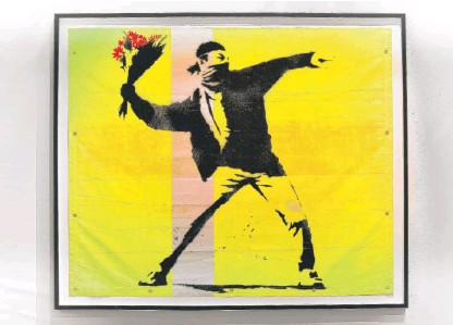 """?? COURTESY THE ART OF BANKSY ?? Banksy, """"Flower Thrower,"""" is among the artist's works featured in """"The Art of Banksy."""""""