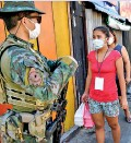 ??  ?? An armed member of the police special action force speaks to residents as he mans a checkpoint in suburban Manila. (AFP)