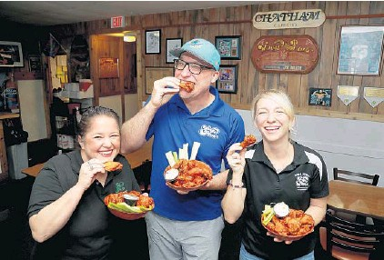 ?? SUSAN STOCKER/SOUTH FLORIDA SUN SENTINEL ?? Bridget Walsh-DeVita, from left, Tom Walsh and Chelsea Walsh on Tuesday at their family-run Wings Plus in Oakland Park, winner of the Let's Wing It contest.