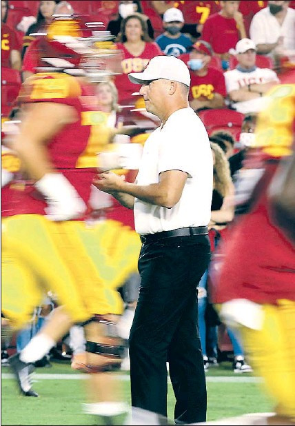 ?? Luis Sinco Los Angeles Times ?? FAN FRUSTRATION HAD already been growing for a long time with Clay Helton, above, watching the Trojans pregame before last Saturday's last-straw 42-28 loss to Stanford — USC's most lopsided loss at home to an unranked opponent since 2000.