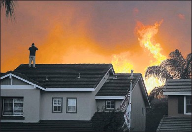 ?? THE ASSOCIATED PRESS ?? Herman Termeer, 54, stood on the roof of his home as the Blue Ridge Fire burned in October in Chino Hills, Calif.