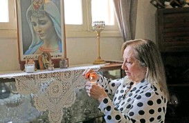 ?? (AFP) ?? Civil war survivor Abla Barotta lights a candle at a shrine in her home in Lebanon's capital Beirut, on April 6
