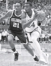 ?? ED ZURGA/GETTY IMAGES ?? Lagerald Vick, driving to the basket against Villanova's Dhamir Cosby-Roundtree, scored 29 points as Kansas improved to 9-0.