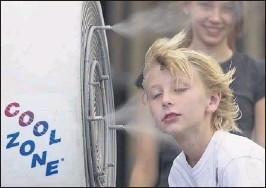 ?? JULIE JACOBSON / ASSOCIATED PRESS ?? Ten-year- old Easton Martin, of Mesa, Ariz., stops to cool off in a misting fan while walking along The Strip with his family Friday in Las Vegas.