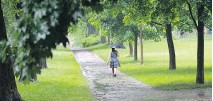 ?? JOHN KENNEY, MONTREAL GAZETTE FILES ?? A woman walks through one of N.D.G.'s parks during a heavy rainfall last June.