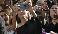 ?? EVAN AGOTINI/INVISION/THE ASSOCIATED PRESS ?? Angelina Jolie takes a selfie with fans. Selfies mean publicists and stars don't have to worry about fake dealers scamming fans.