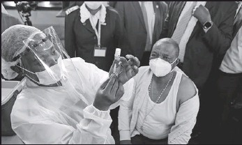 ?? TSVANGIRAYI MUKWAZHI / ASSOCIATED PRESS ?? A nurse prepares to give a shot of Sinopharm vaccine to Zimbabwean Vice-President Constantino Chiwenga at hospital in Harare on Thursday. Chiwenga become the first person in Zimbabwe to receive the jab, marking the first phase of the country's vaccination campaign.