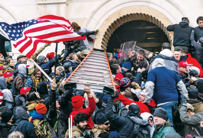 ?? LEV RADIN/SIPA USA/ASSOCIATED PRESS ?? Rioters, who hailed from at least 36 states, along with D.C. and Canada, clash with police using a ladder to try to enter the Capitol through the front doors on Wednesday.