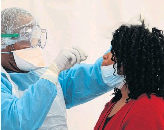 ?? /Sunday Times/Esa ?? Tracking: A health official tests a patient who shows symptoms of Covid 19 in Cape Town. During the week ending August 4, deaths from natural causes declined in most metros.