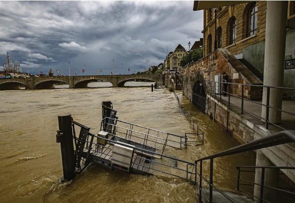 ?? Foto: Patrick Straub (Keystone) ?? Der Rhein bei der Mittleren Brücke in Basel am Mittwoch. Viele Anlegestellen sind bereits unter Wasser.