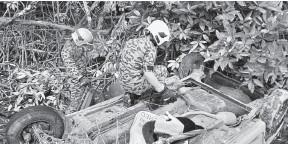 ??  ?? KEMALANGAN: Anggota bomba memeriksa keadaan kereta yang terbalik di dalam longkang.