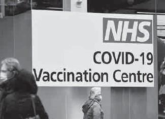 ??  ?? Des gens font la queue pour se faire vacciner contre la Covid-19 dans un centre géré par le NHS, le service public hospitalier anglais, à Londres, le 15 février 2021