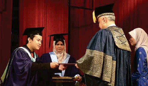 ??  ?? Than Kuan Wei being presented the Royal Education Award.