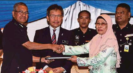 ?? BERNAMA PIC ?? Inspector-General of Police Tan Sri Mohamad Fuzi Harun (left) exchanging documents with TRB Defence Manufacturing Bhd executive chairman Datin Azizah Tuah at the signing of the Designer Rights and the Licensing Agreement on the Commercialisation of...