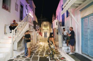 ?? (Louiza Vradi/Reuters) ?? TOURISTS LINGER in front of closed shops and restaurants in Mykonos town yesterday as Greece banned music in restaurants and bars and imposed a nighttime curfew on the island.