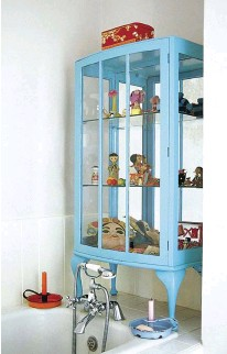 ??  ?? A GLASS-FRONTED CABINET repainted in a tranquil blue is filled with quirky, witty objects for the bather to admire. Its mirrored back reflects light around the room and enhances the feeling of space in the room.