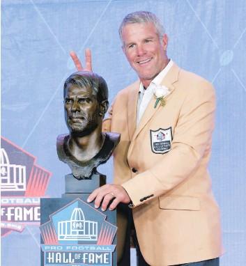 ??  ?? Brett Favre s'est amusé avec les photographes et son buste en bronze, hier soir, lors de son intronisation au Temple de la renommée du football.
