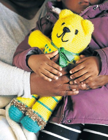 ?? Picture: Esa Alexander ?? A mother comforts her three-year-old daughter, who is clutching her teddy bear, after repeatedly trying to report the girl's rape at police stations in Cape Town last weekend.