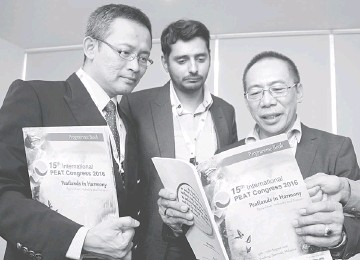 ??  ?? Sulaiman (right) with Shazali and Puvaneswaran browsing through the 15th International Peat Congress programme book. — Photo by Chimon Upon
