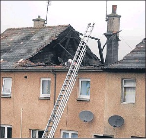 ?? Picture: David Wardle. ?? Left: Firefighters rescue the pet dog from the house. Right: A fire investigator examines the roofspace.