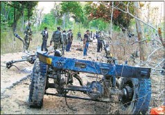 ?? REUTERS ?? Security personnel stand near the wreckage of a police vehicle after a landmine explosion in Bijapur, Chhattisgarh, 2010